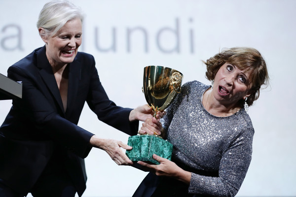 Ariane Ascaride (R) receives the Coppa Volpi for Best Actress Award for Gloria Mundi from Main Competition Jury Member Mary Harron